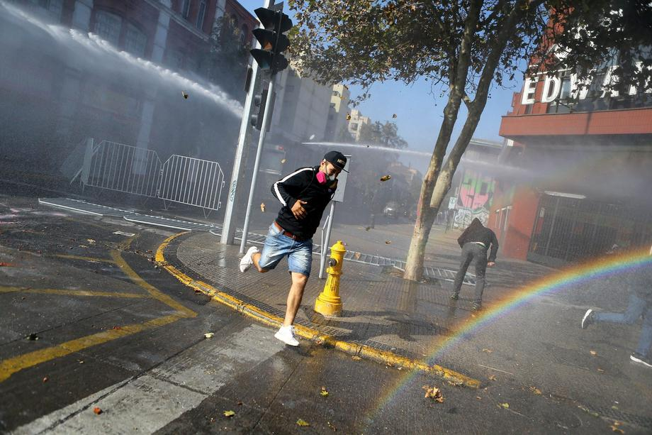 Demonstrators run away from a riot police water canon during a rally in Santiago