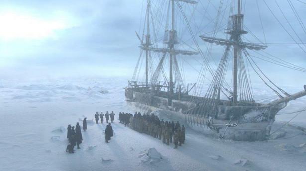 """Serial """"Terror"""" na AMC: Zainspirowany prawdziwymi wydarzeniami serial, którego producentami są Ridley Scott, David Kajganich i Soo Hugh, zabiera widzów w zatrważającą podróż. Akcja produkcji koncentruje się na niebezpiecznej wyprawie Królewskiej Marynarki Wojennej, która wyrusza na nieznane terytorium w poszukiwaniu Przejścia Północno-Zachodniego. Załoga stanie w obliczu zdradliwych warunków, ograniczonych zasobów, gasnącej nadziei na przetrwanie i strachu przed nieznanym. Przenikliwy mróz, samotność i uwięzienie na samym końcu świata – """"Terror"""" świetnie pokazuje, co może pójść źle, gdy grupa mężczyzn desperacko walczących o przeżycie, musi zmierzyć się nie tylko z żywiołami przyrody, ale także ze sobą nawzajem."""