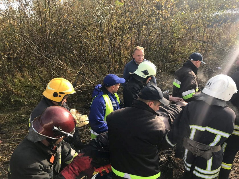 Members of emergency services evacuate a wounded person at the site of the Antonov-12 cargo airplane