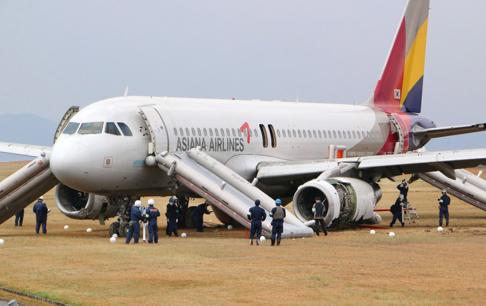Police officers investigate an Asiana Airlines airplane which ran out of runway after landing at Hiroshima airport in Mihara