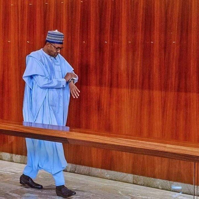 President Muhammadu Buhari checks his timepiece in the power corridors [Twitter/@BashirAhmaad]