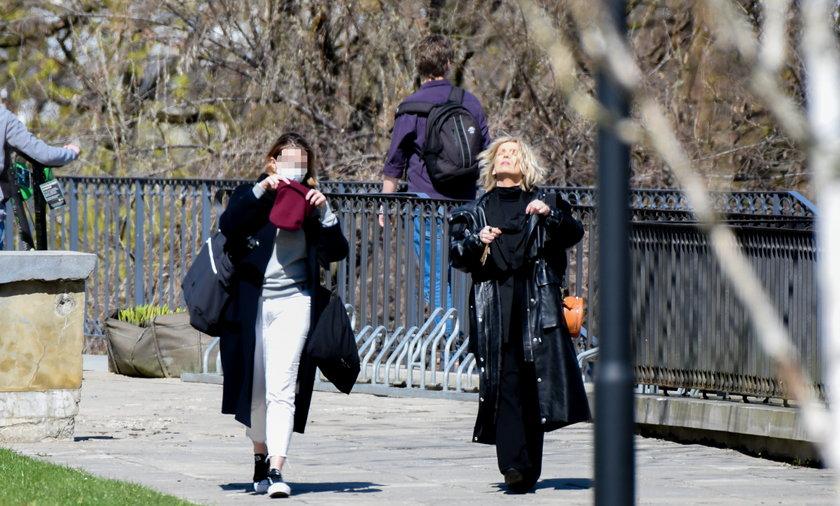 Magda Mołek w stylowej czerni spaceruje po parku.