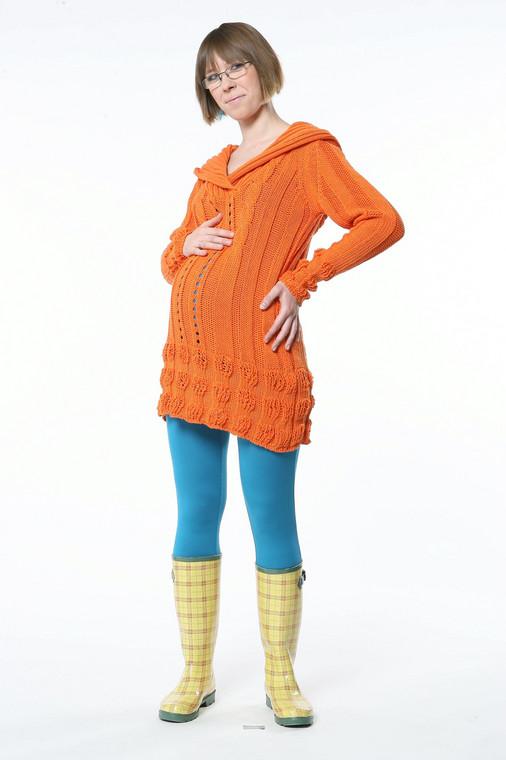 Pomarańczowy luźny sweter to  odważny, ale oryginalny strój dla kobiety w ciąży