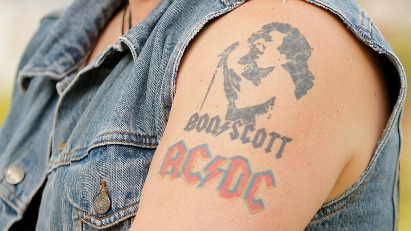 Ramię fana AC/DC z tatuażem przedstawiającym wizerunek Bona Scotta