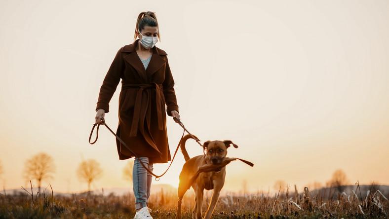 Jesienny spacer z psem, kobieta w maseczce