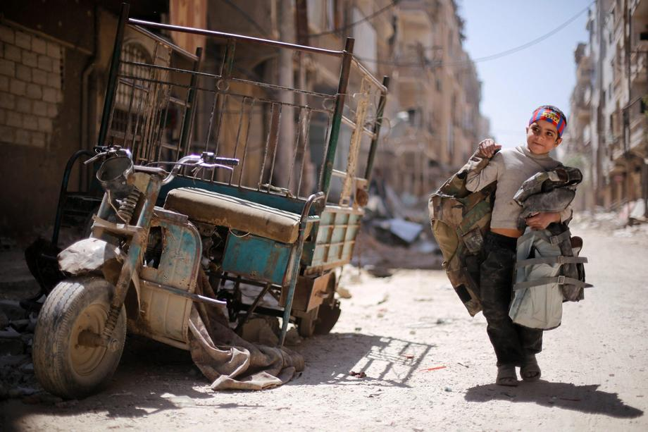 A boy walks along a damaged street at the city of Douma in Damascus