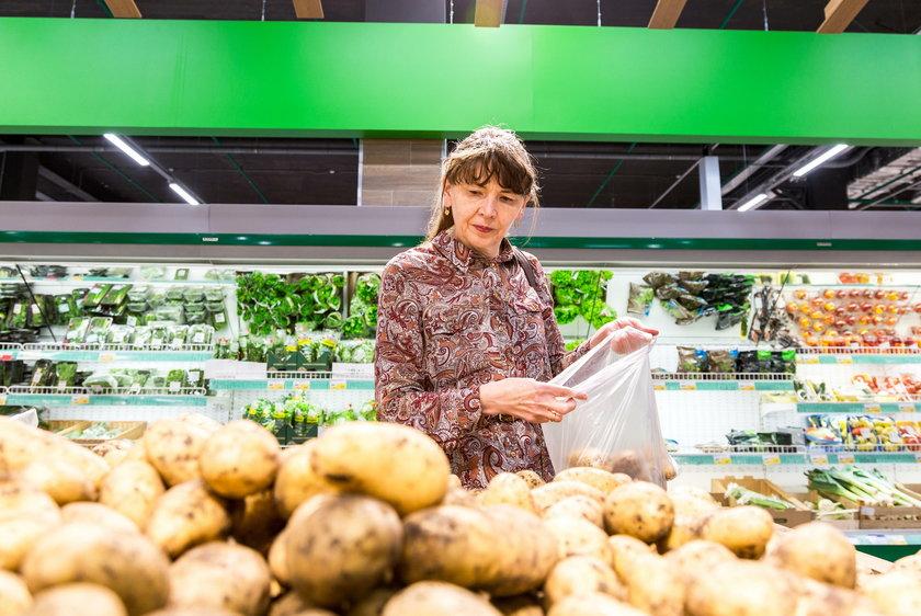 Young woman choosing fresh potatoes
