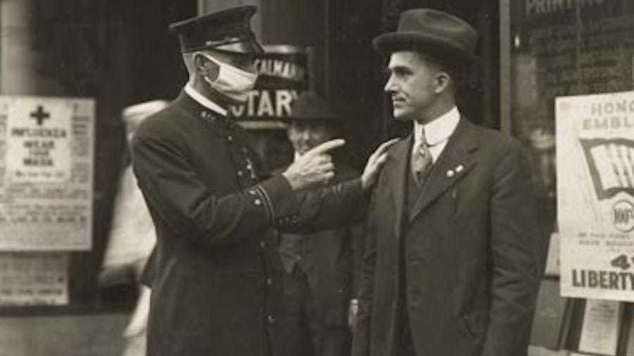 Policjant w masce poucza mieszkańca o obowiązku noszenia maseczek, San Francisco 1918 roku