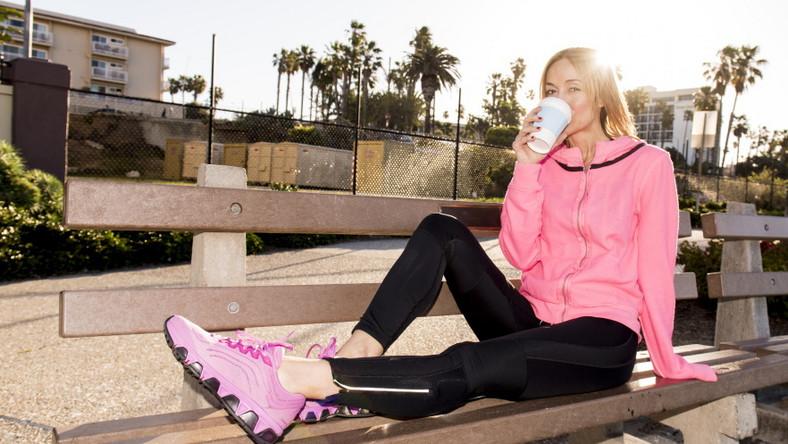 Kobieta po treningu pije kawę