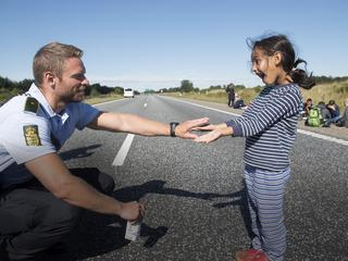 A Danish policeman plays with a migrant girl at the E45 freeway north of Padborg