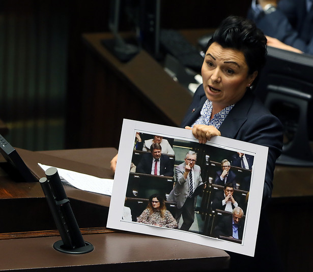 Posłanka PO Monika Wielichowska prezentuje z mównicy sejmowej zdjęcie z nocnej debaty, na którym poseł PiS Piotr Pyzik pokazuje obraźliwy gest w stronę opozycji