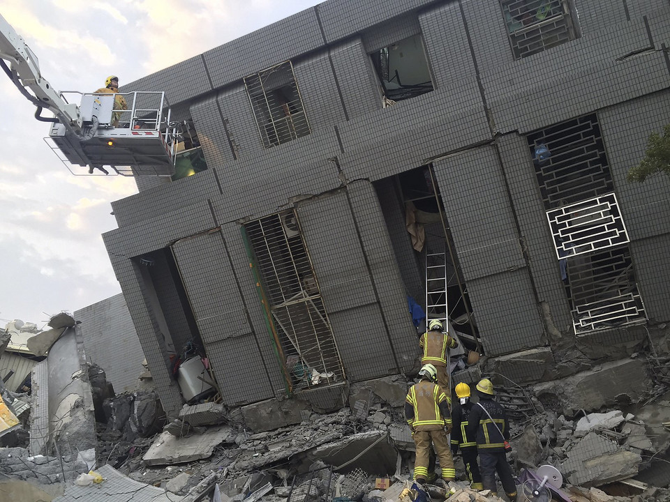 Rescue personnel work at a damaged building after an earthquake in Tainan,