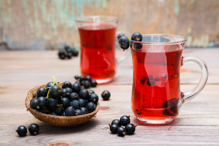 stock-photo-fresh-ripe-black-currant-compote-in-a-glass-and-a-bowl-of-berries-on-a-wooden-table-1458184253