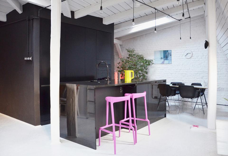 Fioletoworóżowe hokery z tworzywa tworzą graficzny akcent na gładkim czarnym tle wyspy kuchennej.