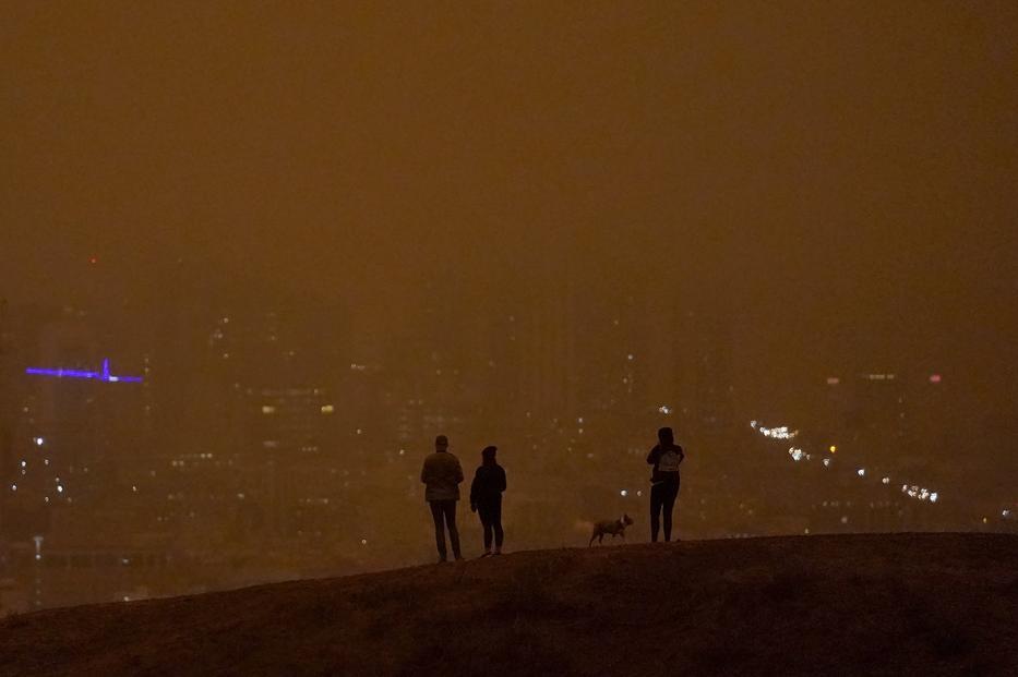 Emberek néznek le egy dombról, de az egész nap égő erdőtűz füstjétől szinte sötét van nappal is San Franciscóban szeptember 9-én / Fotó: MTI/AP/Jeff Chiu