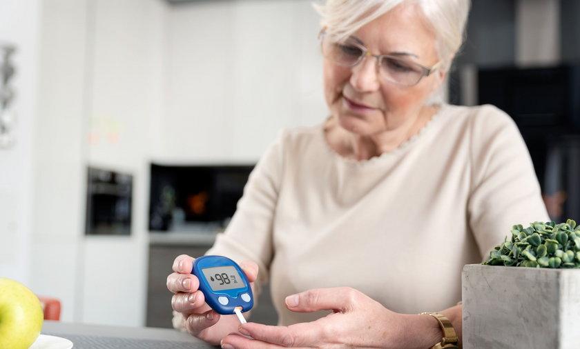 Senior woman checking blood sugar level at home
