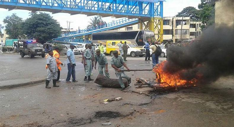 Police and county government askaris remove bonfires lit by traders protesting their eviction at Buxton in Mombasa.