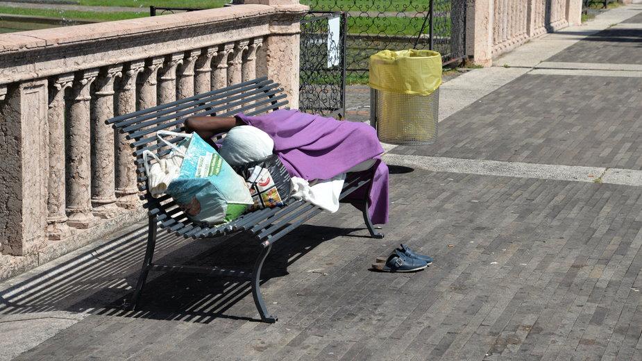 Osoba bezdomna śpiąca na ławce w Genewie, Szwajcaria