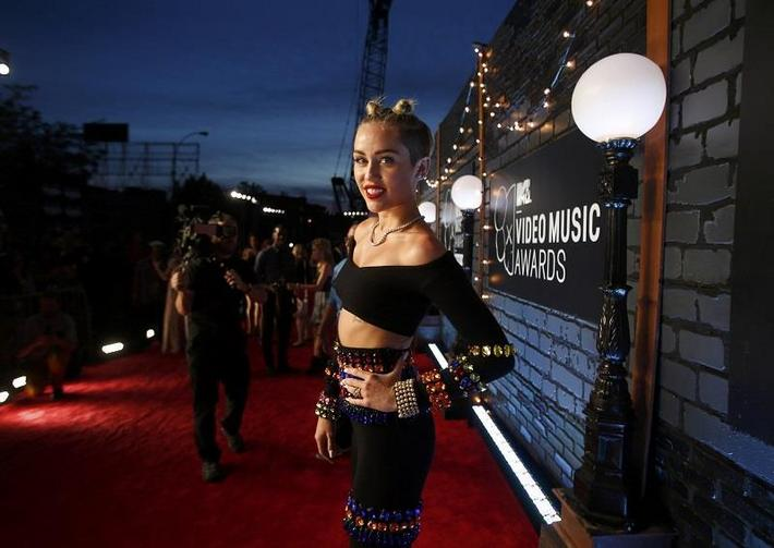 Singer Miley Cyrus poses as she arrives for the 2013 MTV Video Music Awards in New York August 25, 2