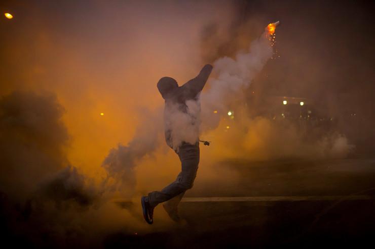 Demonstrant baca suzavac nazad na policiju