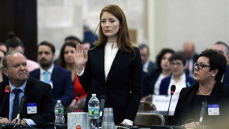 Katie Brennan, the chief of staff at the New Jersey Housing and Mortgage Finance Agency, raises her hand as she is sworn-in to testify before the Select Oversight Committee at the Statehouse on December 4.
