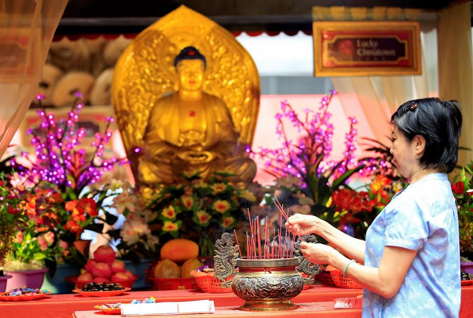 A Filipino-Chinese woman lights incense in front of a Buddha altar display at a Lucky Chinatown mall