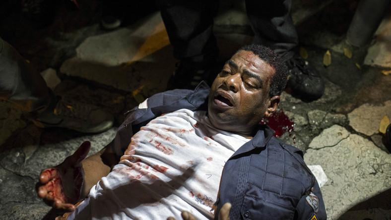 Ranny policjant leży na ziemi po starciach z demonstrantami w Rio de Janeiro