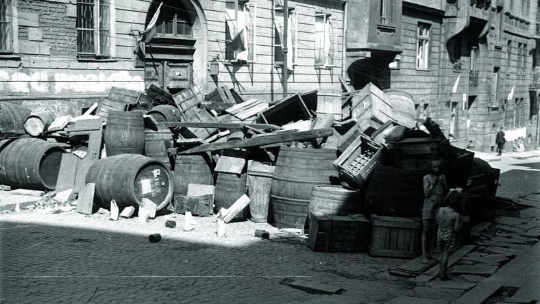 """Między 17 a 20 sierpnia 1944 r., gdy Tadeusz Bukowski zrobił to niepublikowane nigdy zdjęcie barykady na ulicy Tamka, Powiśle nie było jeszcze zagrożone przez Niemców. Jego los zależał od obrony Starówki, o którą toczyła się w tym czasie ciężka bitwa (...) W kadrze """"Bończy"""" widać barykadę przegradzającą brukowaną wówczas ul. Tamka na wysokości domów o numerach 38 i 40 należących do firmy G. Gerlach Fabryka Instrumentów Geodezyjnych i Rysunkowych."""