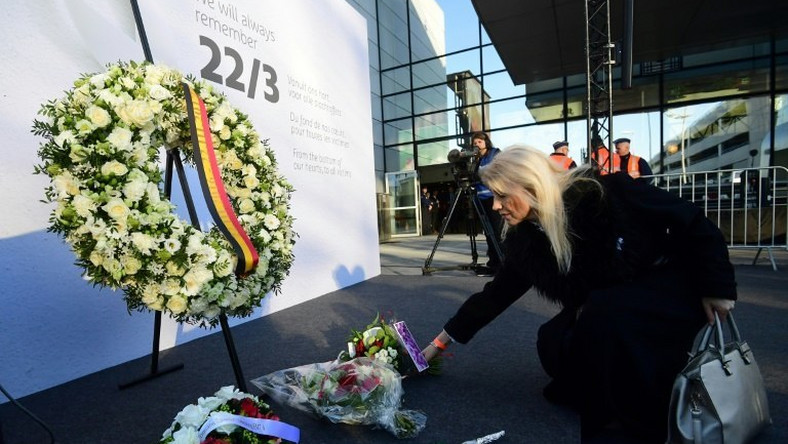 A woman places a bunch of flowers during a memorial at Brussels' international airport in Zaventem