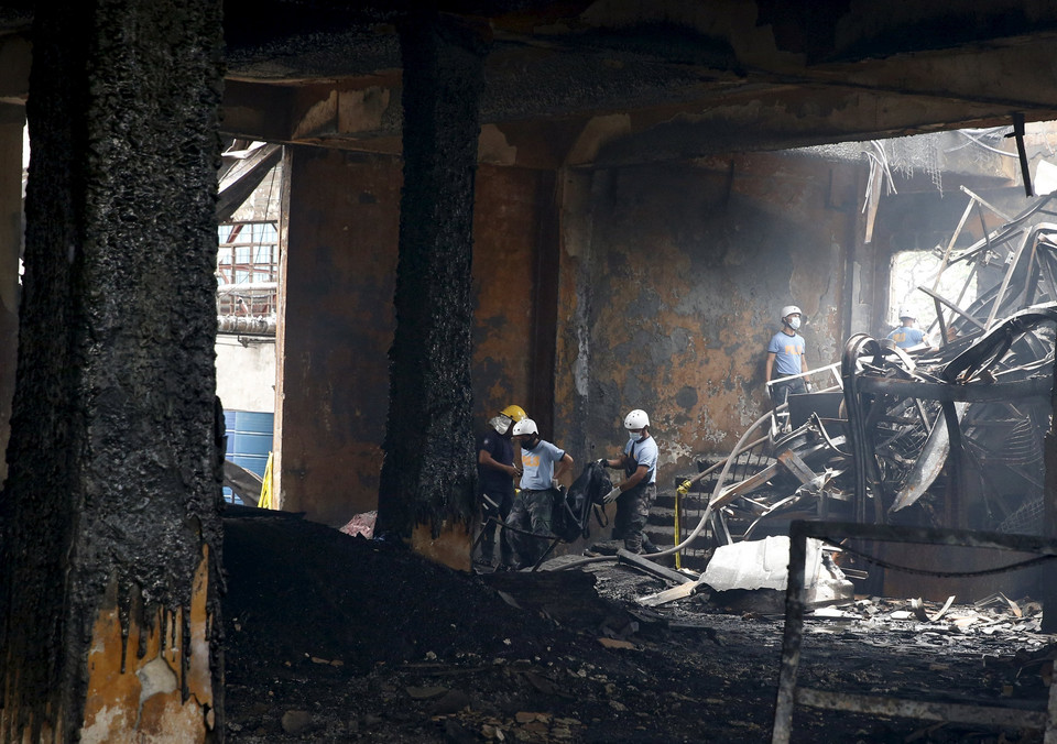 Police rescuers carry a body bag containing a charred remains of a worker inside a gutted footwear factory in Valenzuela