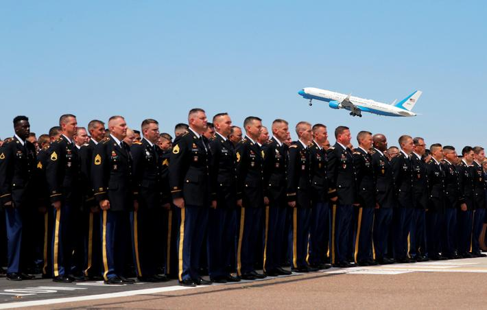 The Arizona National Guard stands at attention as a military transport plane carrying the casket of