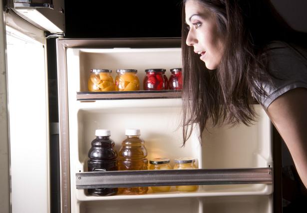 Kobieta zagląda do lodówki