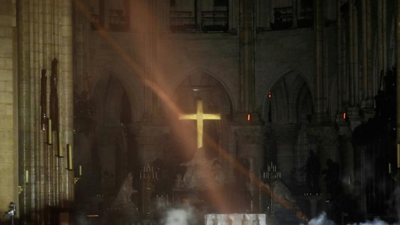Smoke rises around the alter in front of the cross inside the Notre-Dame Cathedral in Paris as firefighters continued to extinguish the blaze on Tuesday