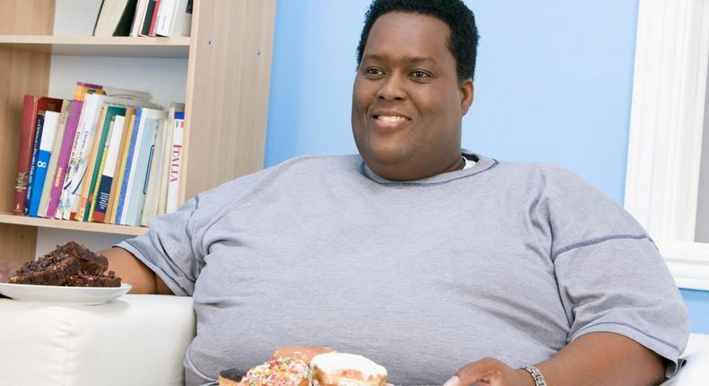 Fat man holding snacks(Ebony Magazine)