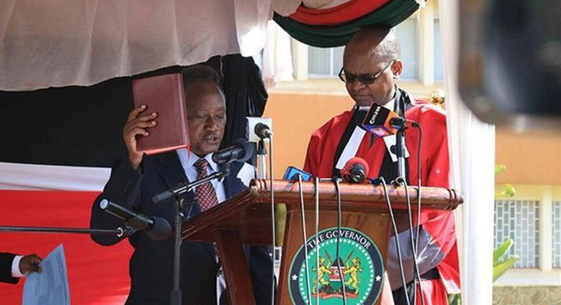 Samuel Wamathai (left) takes oath of office on February 27, 2017. He has pledged to fight corruption in the county.
