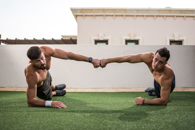 Two handsome shirtless men giving fist bump after successful workout at rooftop gym.