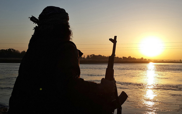 620058_islamic-state-group-fighter-holds-his-ak47-machine-gun-as-he-relaxes-on-the-bank-of-the-euphrates-river-in-raqqa-syria.-ap