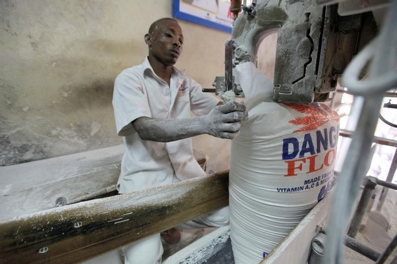 A worker operates a bag-sealing machine at the Dangote flour mill in Apapa district in Nigeria's commercial capital of Lagos November 13, 2010. REUTERS/Akintunde Akinleye