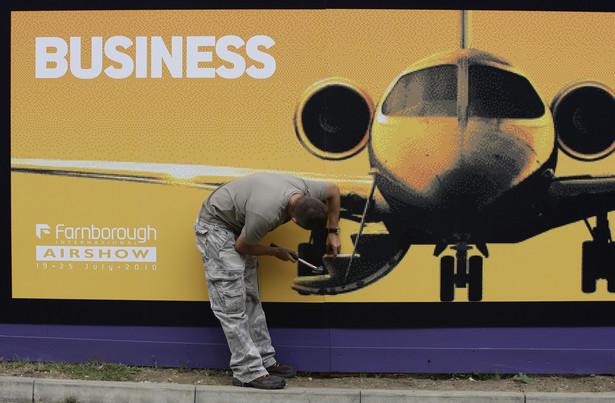 Jeden z pracowników Farnborough International Airshow montuje znak witający gości, fot. Simon Dawson/Bloomberg