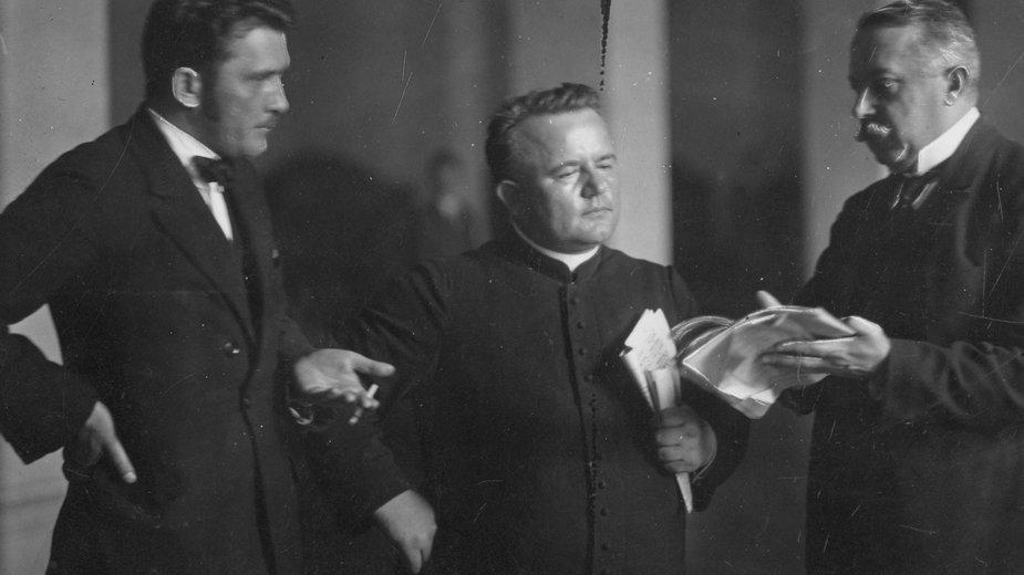 Posłowie w kuluarach sejmowych w trakcie posiedzenia Sejmu w 1925 roku w sprawie ustawy o reformie rolnej. Posłowie od lewej: Ignacy Jasiński, ksiądz Eugeniusz Okoń, Maksymilian Matakiewicz