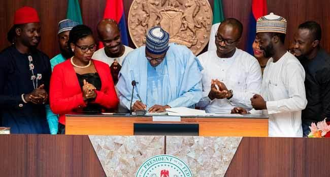 President Buhari signing the Not Too Young To Run Bill (Channels)