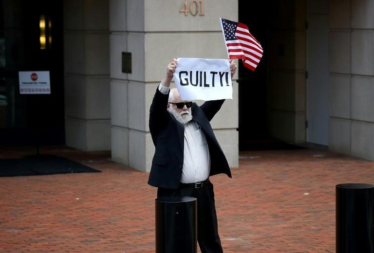 A lone protester holds up a sign and an American flag outside the Alexandria courthouse after former Trump campaign chairman Paul Manafort was found guilty of tax crimes and bank fraud