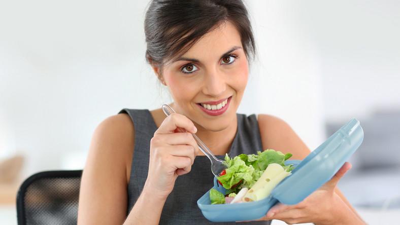 Kobieta je lunch przy biurku
