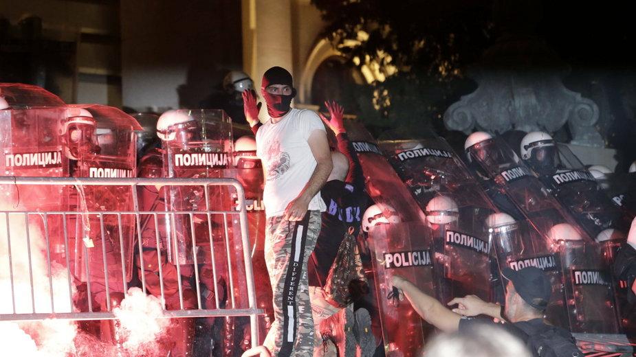 Protestujący mężczyzna na tle oddziałów policji w Belgradzie.