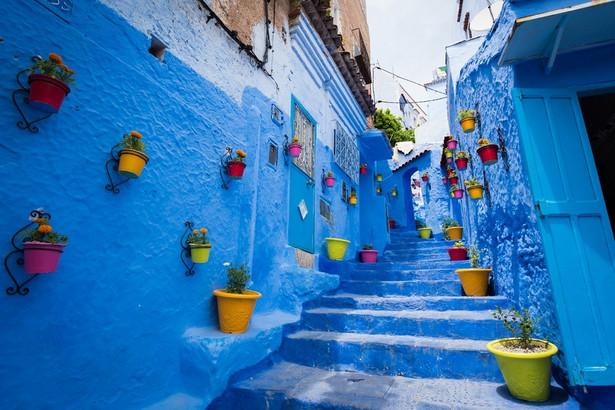 """Chefchaouen """"Niebieskie Miasto"""" jak zwykło się określać Chefchaouen położone jest w północno-zachodniej części Maroka, pośród skalistego pasma górskiego Rif, określającego fizyczną granicę między Europą i Afryką. To świetne miejsce na wędrowanie i popijanie miętowej herbaty. Jest tu bardzo spokojnie, ale miejsce to potrafi też oszołomić. Niemal wszystkie budynki są pomalowane żywym błękitem, ale zabudowa wcale nie jest przez to monotonna – można tu chyba zobaczyć każdy odcień tego koloru: błękit, indygo, kobalt, lazur, cyjan, szafir… nieskończona gama odcieni sprawia, że miasto wydaje się wręcz tryskać kolorami, a marokańskie łuki tylko podkreślają wyjątkowość tej architektury. Trudno porównać Chefchaouen z jakimkolwiek innym miastem na świecie. Zabudowania wkomponowane pomiędzy strome zbocza, wiszące tuż nad urwiskiem przypominać mogą nieco Santorini – tam jednak błękit wyłania się z wód widocznych na horyzoncie, tutaj błękitne są niemal wszystkie budynki, a zamiast morza dookoła roztaczają się góry. Pobyt w tym miejscu nie może się wręcz obejść bez górskiej wycieczki. Warto wybrać się zwłaszcza nad Cascades d'Akchour, parę wodospadów (górna kaskada ma około stu metrów, niższa około dwudziestu) położoną w górach, około 45 minut od miasta. Malownicza trasa prowadzi między innymi przez naturalny most zwany Mostem Boga, a na miejscu można popływać w otoczonym bujną roślinnością, krystalicznie czystym, turkusowym basenie. Źródło: r.pl/maroko >>"""