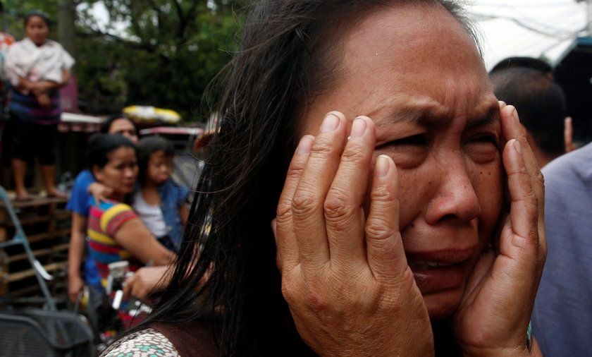 A family friend weeps after Nora Acielo, 47, was gunned down by unidentified men while escorting her two children to school in Manila