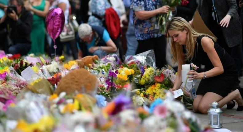 People lay flowers in tribute to the victims of the May 22 bomb attack in Manchester in northern England