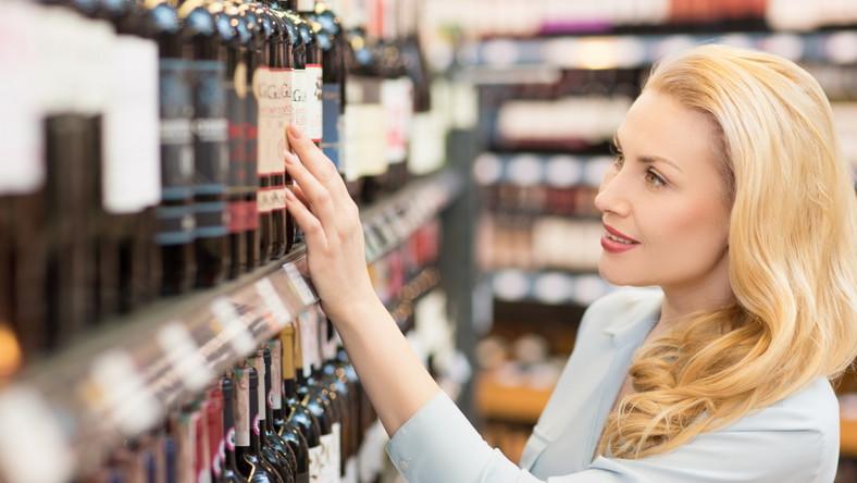 Kobieta wybiera wino w sklepie