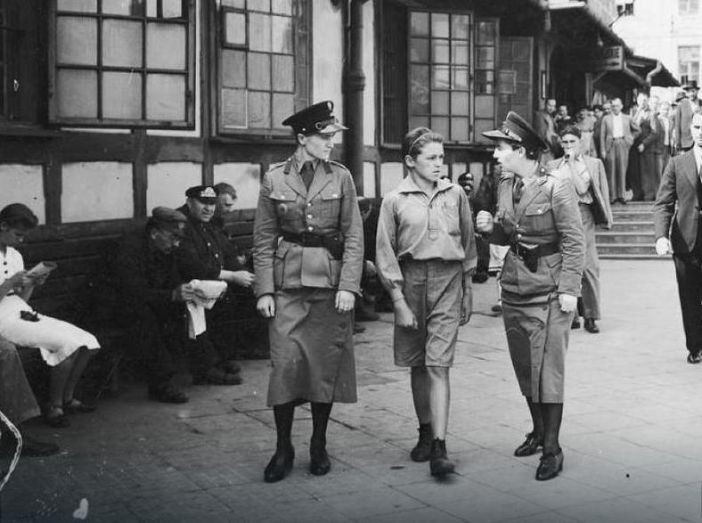 Policjantki prowadzą młodego kieszonkowca do izby zatrzymań ulicami Warszawy w roku 1939