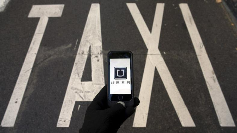 The logo of car-sharing service app Uber on a smartphone over a reserved lane for taxis in a street is seen in this December 10, 2014 file photo illustration. REUTERS/Sergio Perez/Illustration/Files